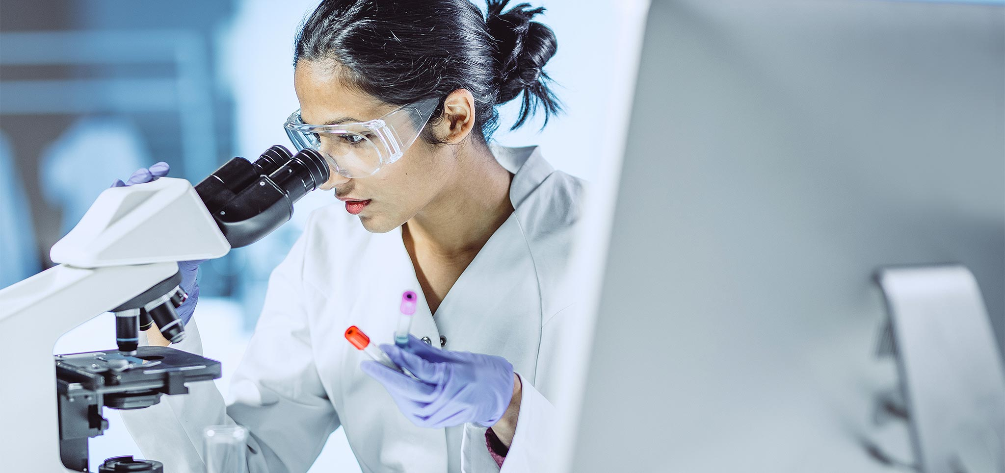 Female scientist operating a microscope